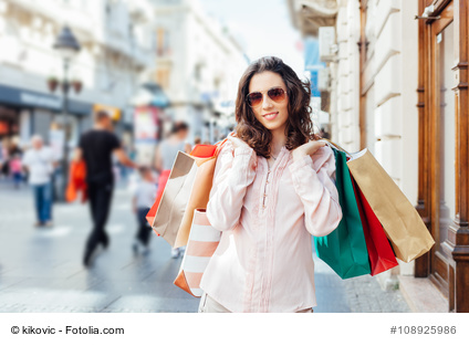 Happy woman holding shopping bags after shopping in the city with copy space