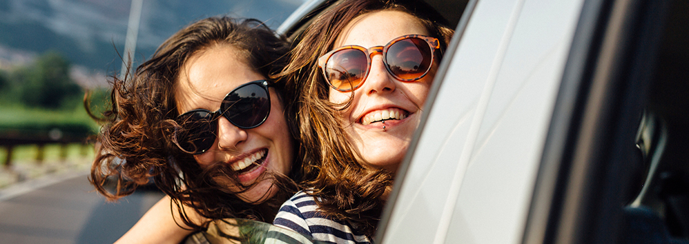 young women friends enjoying car trip.